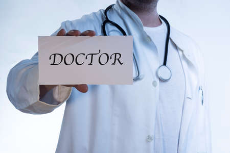 doctor in white shirt wearing a stethoscope around his neck holding a sign that says DOCTOR