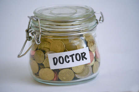 jar full of coins with a DOCTOR sign on it Banque d'images