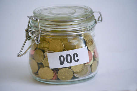 jar full of coins with a DOC sign on it