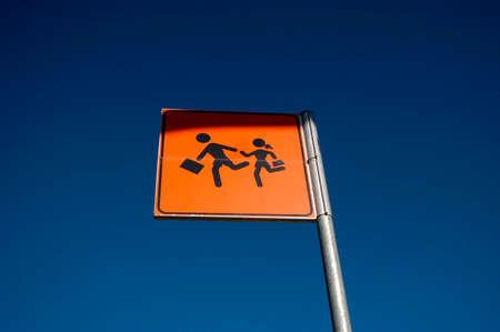 pedestrian traffic sign on the street, orange sign, blue sky
