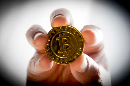 holding a golden bitcoin coin in hand, representing the electronic currency
