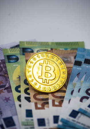 a golden bitcoin coin on banknotes, representing the electronic currency