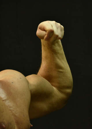 a bodybuilder showing his muscles, fitness and health in bodybuilding