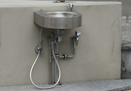 a wash basin or sink with a tap for washing hands