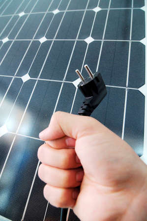 a power plug and solar panel, sustainable and ecological energy production Stockfoto