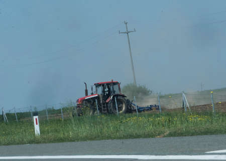 Tractor plowing the field in spring, farm work in agriculture