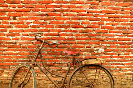 uncoated: an old bicycle propped against the old wall wall