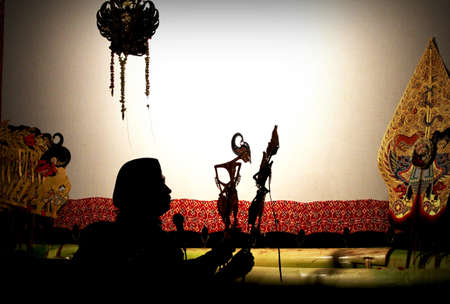 shadow puppet: A master of Javanese puppet  puppeteer  performing shadow puppet