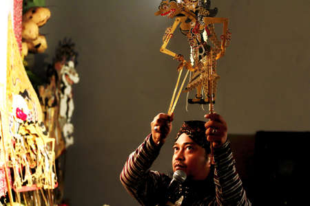 A master of Javanese puppet  puppeteer  performing shadow puppet