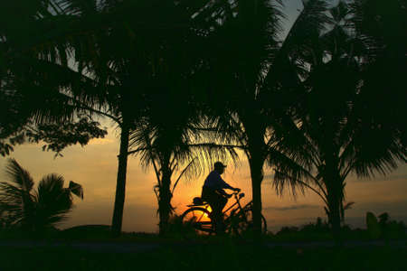 Silhouette of cycling in the sunset at country side photo