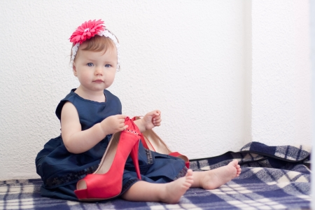 Child is holding adult high heel shoe Stock Photo - 20670301