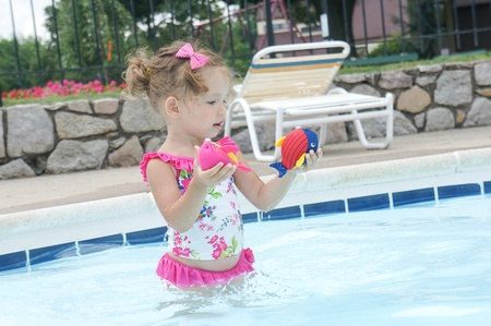 expressing: Cute baby girl is having fun in the pool Stock Photo