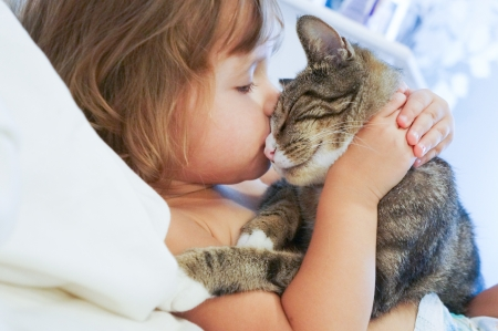 kissing love: baby girl and the kitty Stock Photo