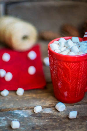 Red knit mug with hot chocolate and marshmallows on wooden background