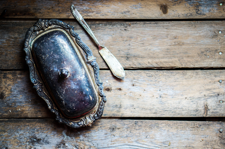Vintage silver butter dish on wooden background