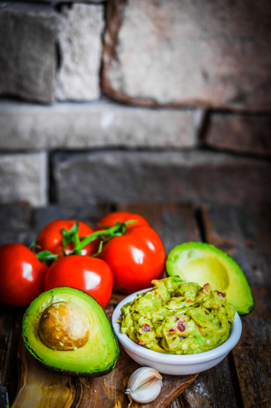 Guacamole   and avocado on rustic wooden background