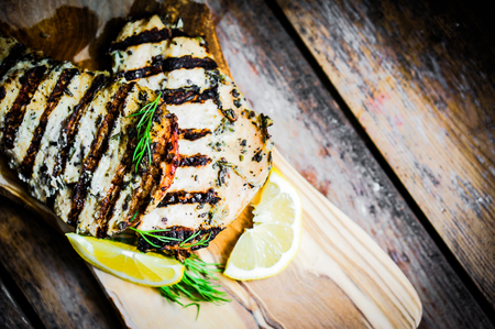 Grilled chicken with herbs and lemon on wooden background Zdjęcie Seryjne