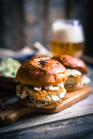 gourmet burger: Rustic fish burgers with coleslaw and beer Stock Photo