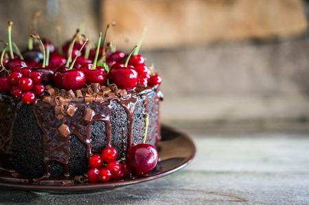 チェリーの木製の背景とチョコレート ケーキ 写真素材