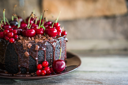 Chocolate cake with cherries on wooden background Фото со стока