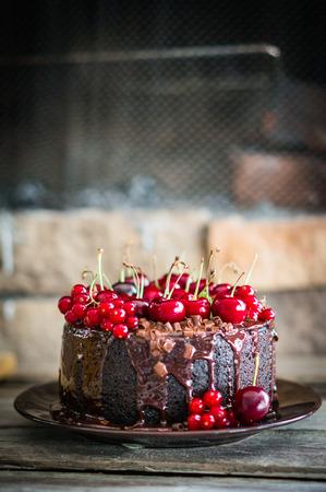 fresh cream: Chocolate cake with cherries on wooden background Stock Photo