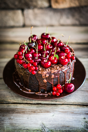 Chocolate cake with cherries on wooden background Imagens