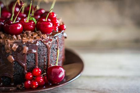 나무 배경에 체리와 초콜릿 케이크