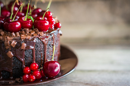 fruit cake: Chocolate cake with cherries on wooden background Stock Photo