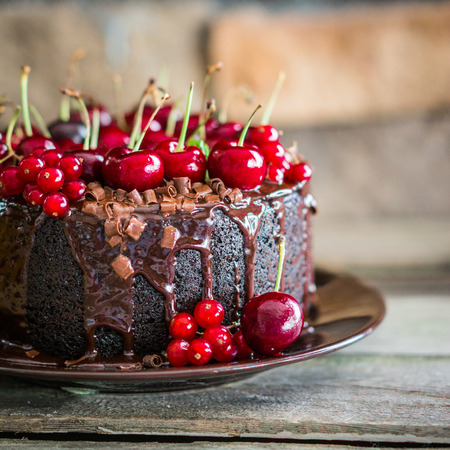 Chocolate cake with cherries on wooden background Stockfoto