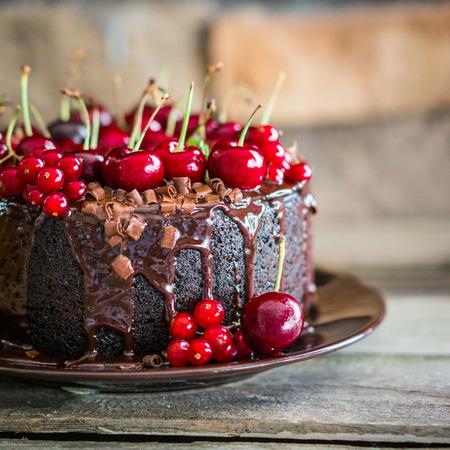 porcion de torta: Pastel de chocolate con cerezas en el fondo de madera Foto de archivo