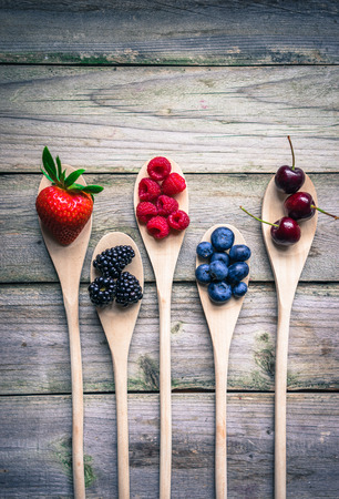 wooden spoon: Berries on wooden rustic background