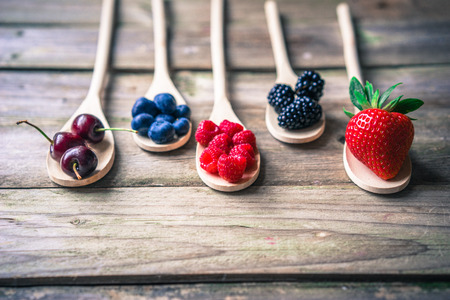 eating fruit: Berries on wooden rustic background