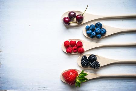 spoon: Berries on wooden background