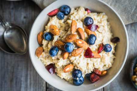 rustic food: Oatmeal with berries and nuts Stock Photo
