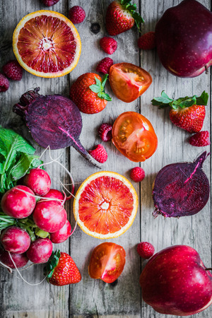 Red fruits and vegetables on wooden background photo