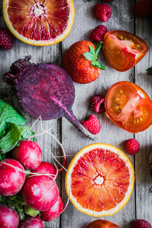 red: Red fruits and vegetables on wooden background Stock Photo
