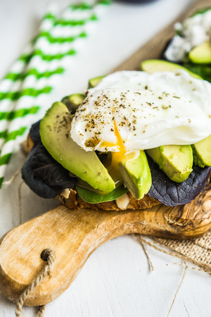 Healthy sandwich with avocado and poached eggs photo