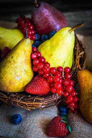 Pears with berries on wooden background photo