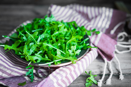 Arugula salad on wooden background