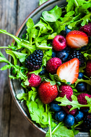 close up: Green salad with arugula and berries