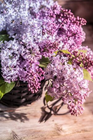 Bouquet of lilacs on wooden background photo