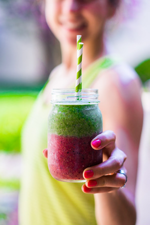Fitness girl with colorful smoothie