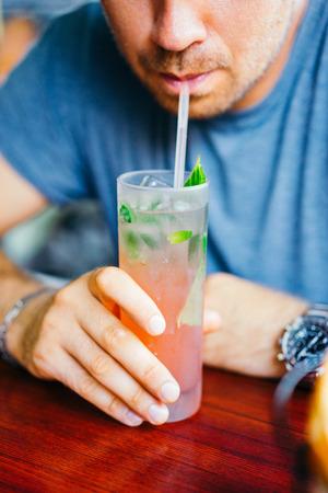 alimentos y bebidas: El hombre joven está bebiendo cócteles al aire libre
