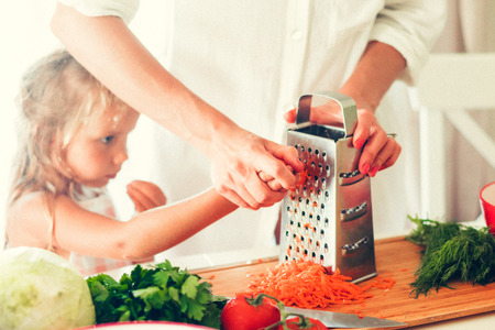 The woman is cooking at the kitchen with daughter ( grating carrots )