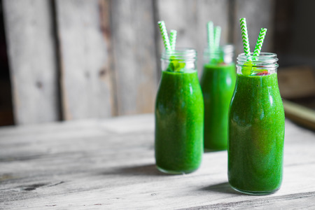 Fresh green smoothie on rustic wooden background
