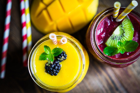 smoothie: Colorful two layer smoothies with mango and berries on rustic wooden background Stock Photo
