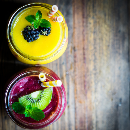 mango: Colorful two layer smoothies with mango and berries on rustic wooden background Stock Photo