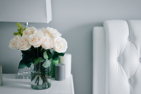 Bouquet of white pastel roses in white interior
