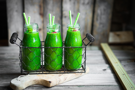 batidos de frutas: Batido verde fresco en el fondo de madera rústica