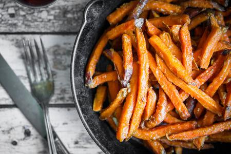 batata: Patatas fritas de camote en sartén de hierro fundido en el fondo de madera